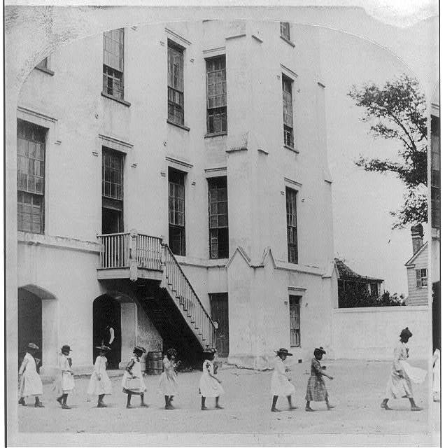 Photograph of students following a teacher in the schoolyard at Simonton School, B.W. Kilburn, circa 1891, courtesy of Library of Congress.
