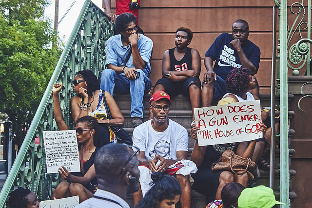Black Lives Matter protestors sitting on the steps of the Daughters of the Confederacy at the end of the march, photograph by Zach NeSmith, June 20, 2015, Charleston, South Carolina.