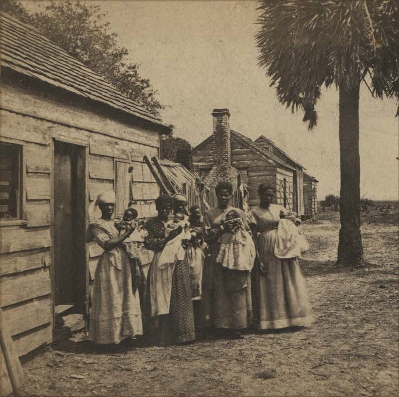 Group of African American women, enslaved or newly freed, holding babies outside cabins, Sam A. Cooley, Port Royal, South Carolina, circa 1860, courtesy of the Beaufort County Library.