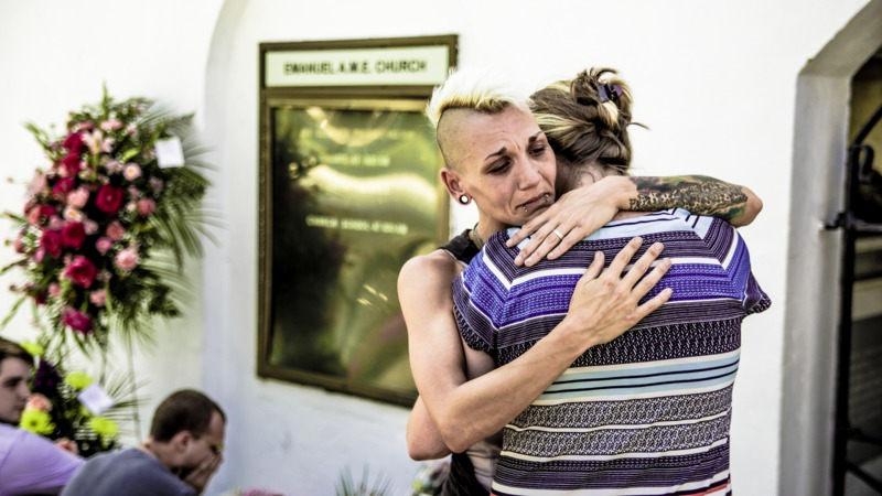 Visitors embrace outside the Emanuel AME Church, photograph by Hunter Boone, June 21, 2015, Charleston, South Carolina.