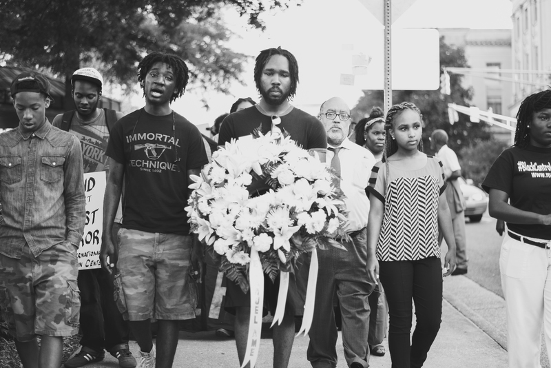 Marchers walking from the Georgia State Capital to Big Bethel AME Church carry a wreath in honor of the victims at Emanuel AME Church, photograph by Calvin Lionel, June 19, 2015, Atlanta, Georgia.