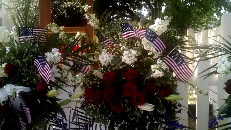 Flowers with American flags left by visitors at the Emanuel AME Church, photograph by Toni Carrier, June 29, 2015, Charleston, South Carolina.
