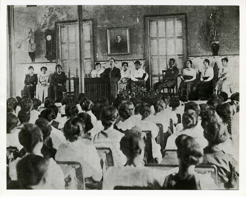 Principal Benjamin Cox addressing the student body during a meeting in Avery's auditorium with faculty seated behind him, Charleston, South Carolina, ca. 1916, courtesy of the Avery Research Center.