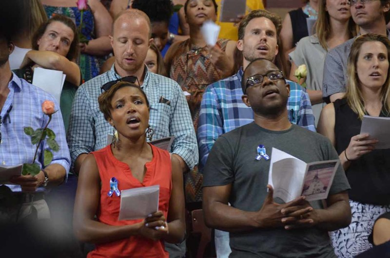 "Attendees singing at the City of Charleston prayer vigil, June 19, 2015, Charleston, South Carolina, courtesy of ABC New4 WCIV-TV.  The vigil opened with ""Amazing Grace,"" performed by the Charleston Police Pipes and Drum, and closed with the crowd singing ""We Shall Overcome."""
