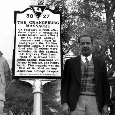 Cleveland Sellers stands beside historic marker on S.C. State University campus at the 2000 Orangeburg Massacre memorial, Orangeburg, South Carolina, image courtesy of Cecil Williams.