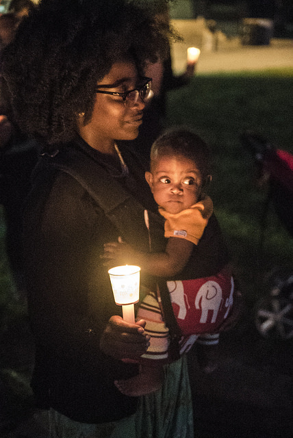 A woman with a baby holds a candle at a Black Lives Matter vigil, June 19, 2015, Madison, Wisconsin, courtesy of Light Brigade.