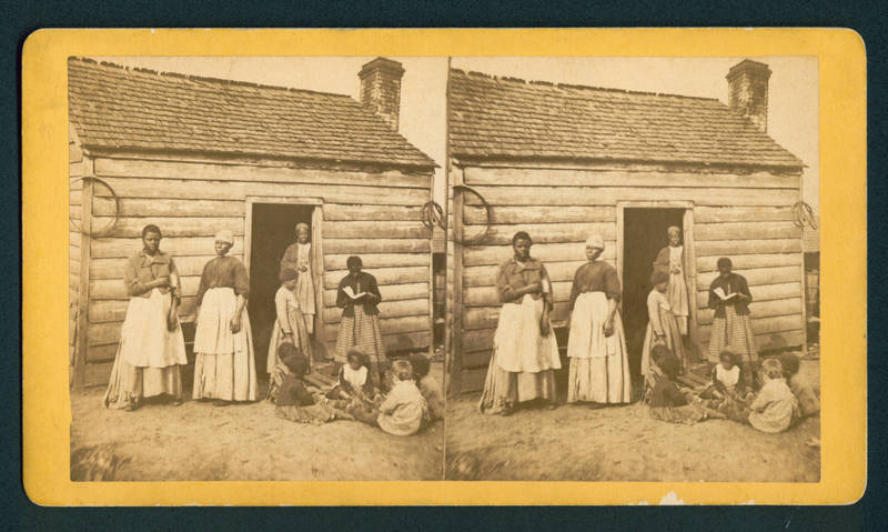 "Newly freed women and children outside of a home labeled as ""Aunt Betsey's Cabin,"" steroscopic photograph by J.A. Palmer, Aiken, South Carolina, 1875, courtesy of South Caroliniana Library at the University of South Carolina."