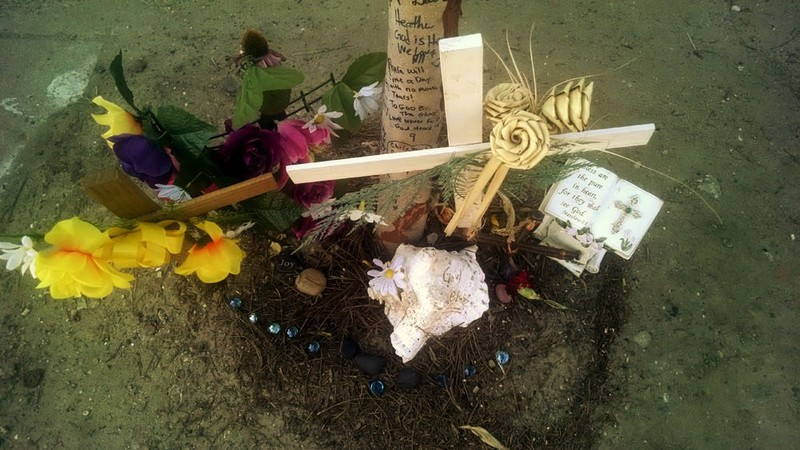 Base of a tree covered in messages and prayers surrounded by memorabilia outside of the Emanuel AME Church, photograph by Toni Carrier, June 29, 2015, Charleston, South Carolina.