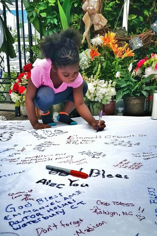 A young girl signs one of several posters put up in the weeks following the mass shooting at Emanuel AME Church, June 25, 2015, Charleston, South Carolina, courtesy of ABC New4 WCIV-TV.
