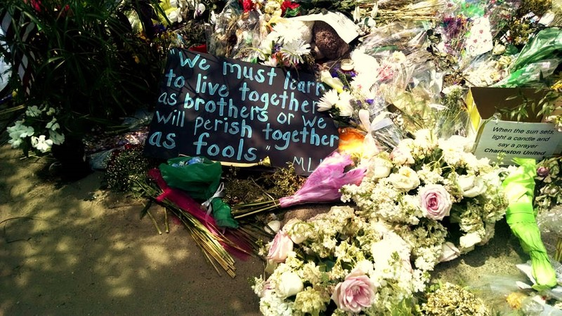 A poster featuring a quote by Dr. Martin Luther King left among flowers at the Emanuel AME Church, photograph by Toni Carrier, June 23, 2015, Charleston, South Carolina.