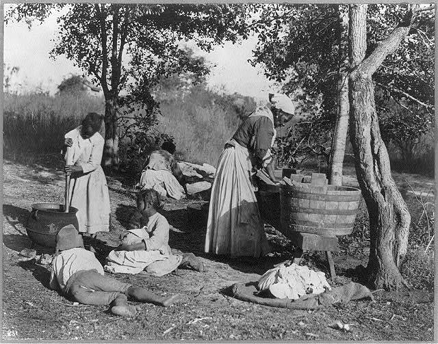 Photograph of a group of women and children doing laundry with a scrub board and tub, circa 1900, courtesy of the Library of Congress.