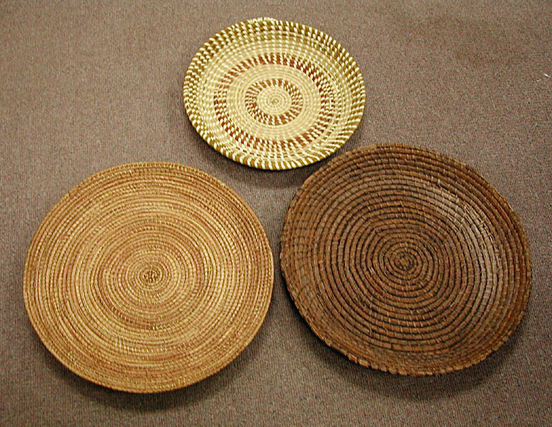 Fanner baskets, used for winnowing rice, courtesy of Drayton Hall. In October, enslaved workers on Lowcountry rice plantations fanned the threshed grain in wide, flat baskets made by African basket-makers. These three baskets look strikingly similar, and demonstrate the continuation of this agricultural technique and art form from West Africa to the Lowcountry. The light brown basket on the left is from Senegal; the dark brown basket on the right belongs to the Drayton family and was made before the U.S. Civil War; the white basket at the top of the picture was made by an African American sweetgrass basket maker in Mount Pleasant, South Carolina in the early 2000s.