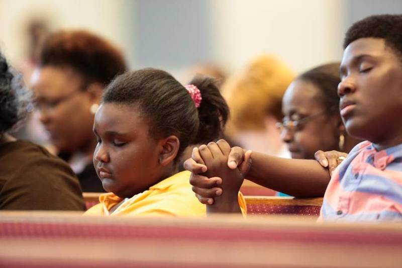 Children pray at the Kenneth Monroe Transformation Center of the AME Zion Church at a vigil for victims of the Charleston shooting at Emanuel AME Church, June 18, 2015, Rock Hill, South Carolina, courtesy of <em>The Herald</em>.