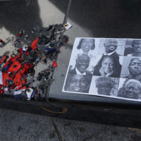 Confederate flag ashes next to photographs of the nine victims killed in the mass shooting at the NYC Stands with Charleston Vigil and Rally, photograph by All-Nite Images, June 22, 2015, New York, New York.
