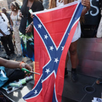 Protesters destroying a Confederate flag at the NYC Stands with Charleston Vigil and Rally, photograph by The All-Nite Images, June 22, 2015, New York, New York. Protests against the Confederate flag grew across the nation after the Emanuel AME Church shooting, particularly after photos emerged of shooter Dylann Roof posing with the flag.