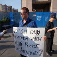 Man holding a sign at NYC Stands with Charleston Vigil and Rally, photograph by The All-Night Images, June 22, 2015, New York, New York.