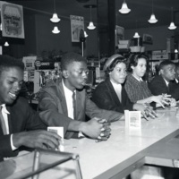 Burke High School students at a sit-in at the S.H. Kress store on King Street, Charleston, South Carolina, April 1, 1960, photograph by Bill Jordan, courtesy of the <em>Post and Courier</em>. Eugene Hunt, Avery graduate and Burke High School teacher, encouraged students to join this sit-in as challenge to segregationist policies and participate in the larger Charleston Movement for Civil Rights. Averyite J. Arthur Brown's daughter Minerva (fourth from left) was one of the participants.