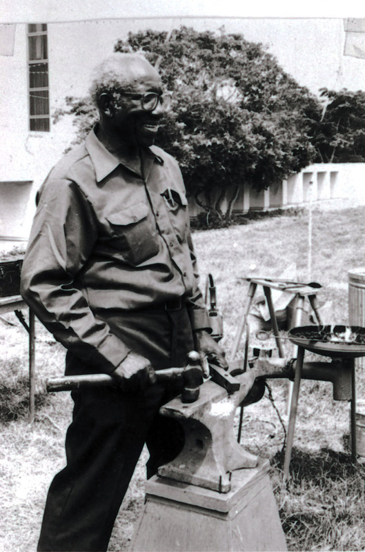 Philip Simmons standing at his anvil with hammer, Charleston, South Carolina, ca. 1993, Philip Simmons Collection, courtesy of the Avery Research Center.