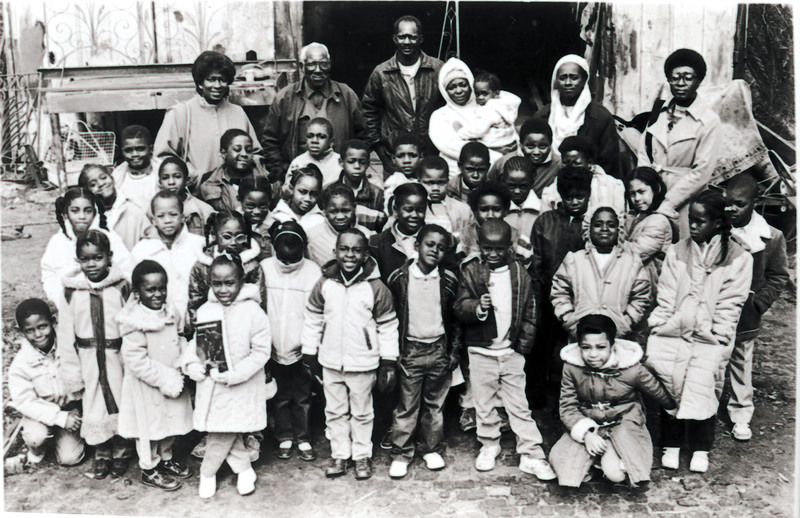 Philip Simmons and a group of children in front of his workshop, ca. 1995, Philip Simmons Collection, courtesy of the Avery Research Center.