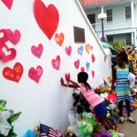 A young girl places a heart on the Emanuel AME Church at a Young Preservationists' event, photograph by Brittany Lavelle Tulla, July 8, 2015, Charleston, South Carolina.